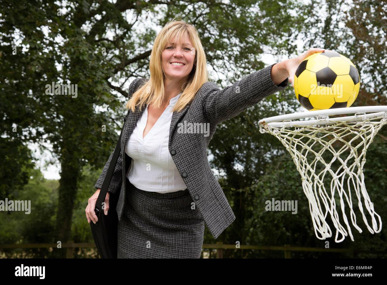 La empresaria alcanzar su meta bajando una pelota en una red Imagen De Stock