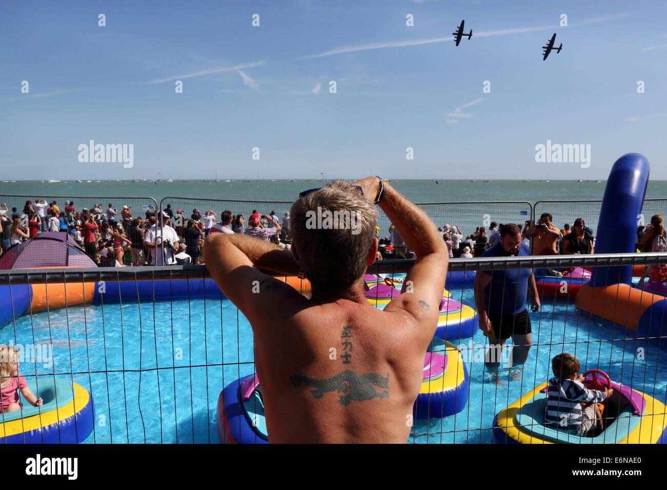 Las multitudes en la playa, disfrutar del sol durante la visualización de aire Aibourne en Eastbourne, Sussex, Imagen De Stock
