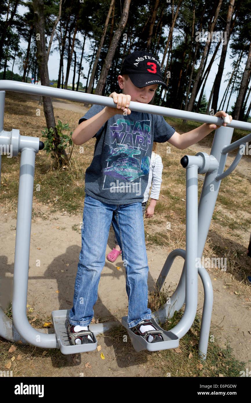 Polish boy 8 años jugando en el parque de la ciudad máquina de ejercicio. Rawa Mazowiecka Polonia Imagen De Stock