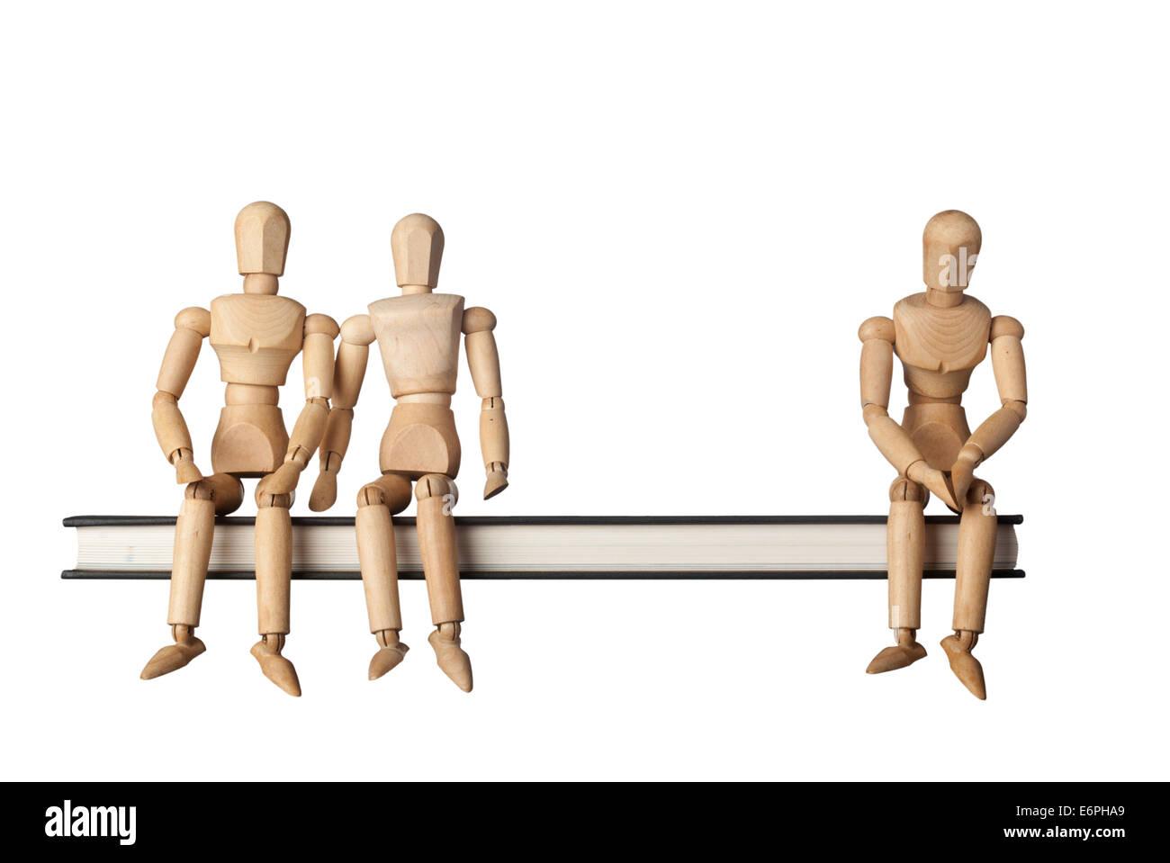 Relación entre tres personas representadas por tres figuras aisladas sobre fondo blanco. Imagen De Stock