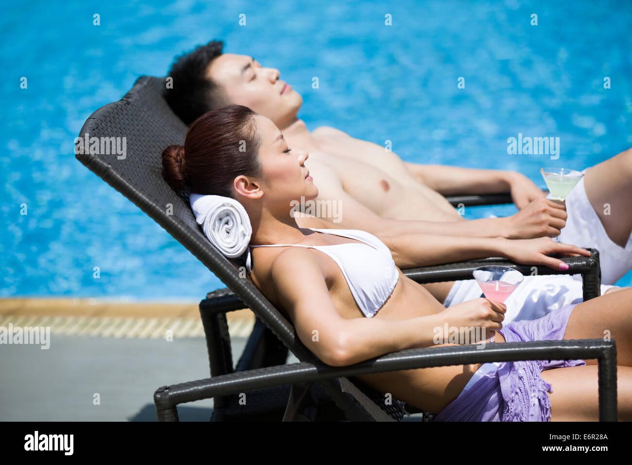 Pareja joven tomando el sol en la piscina. Foto de stock
