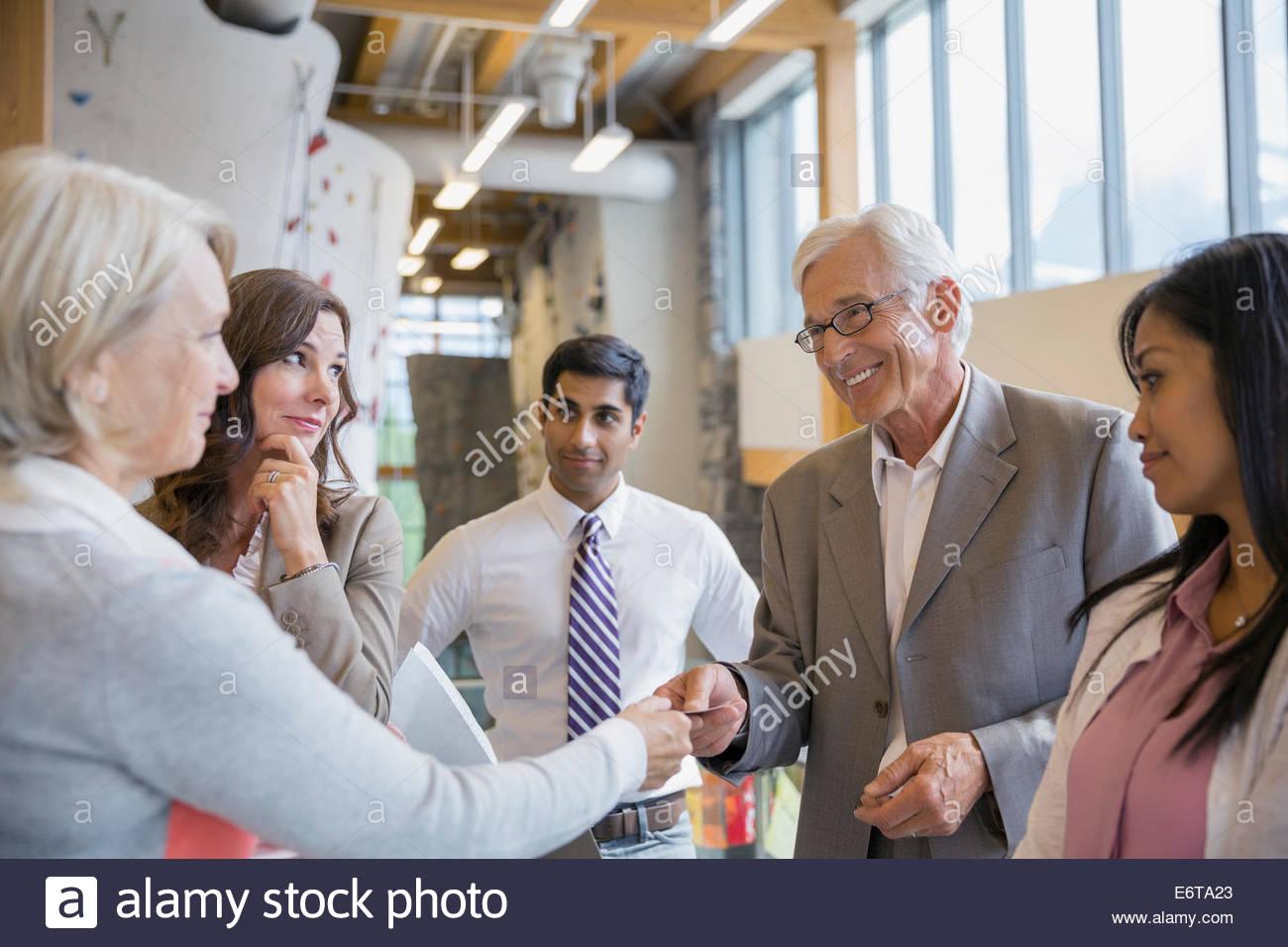 La gente de negocios de intercambiar tarjetas de visita en el vestíbulo de la oficina Imagen De Stock