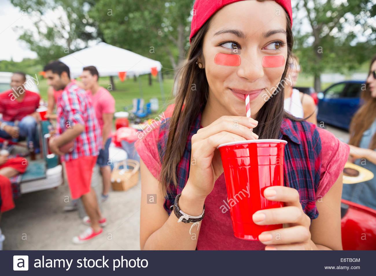 Mujer bebiendo en barbacoa en el campo Imagen De Stock