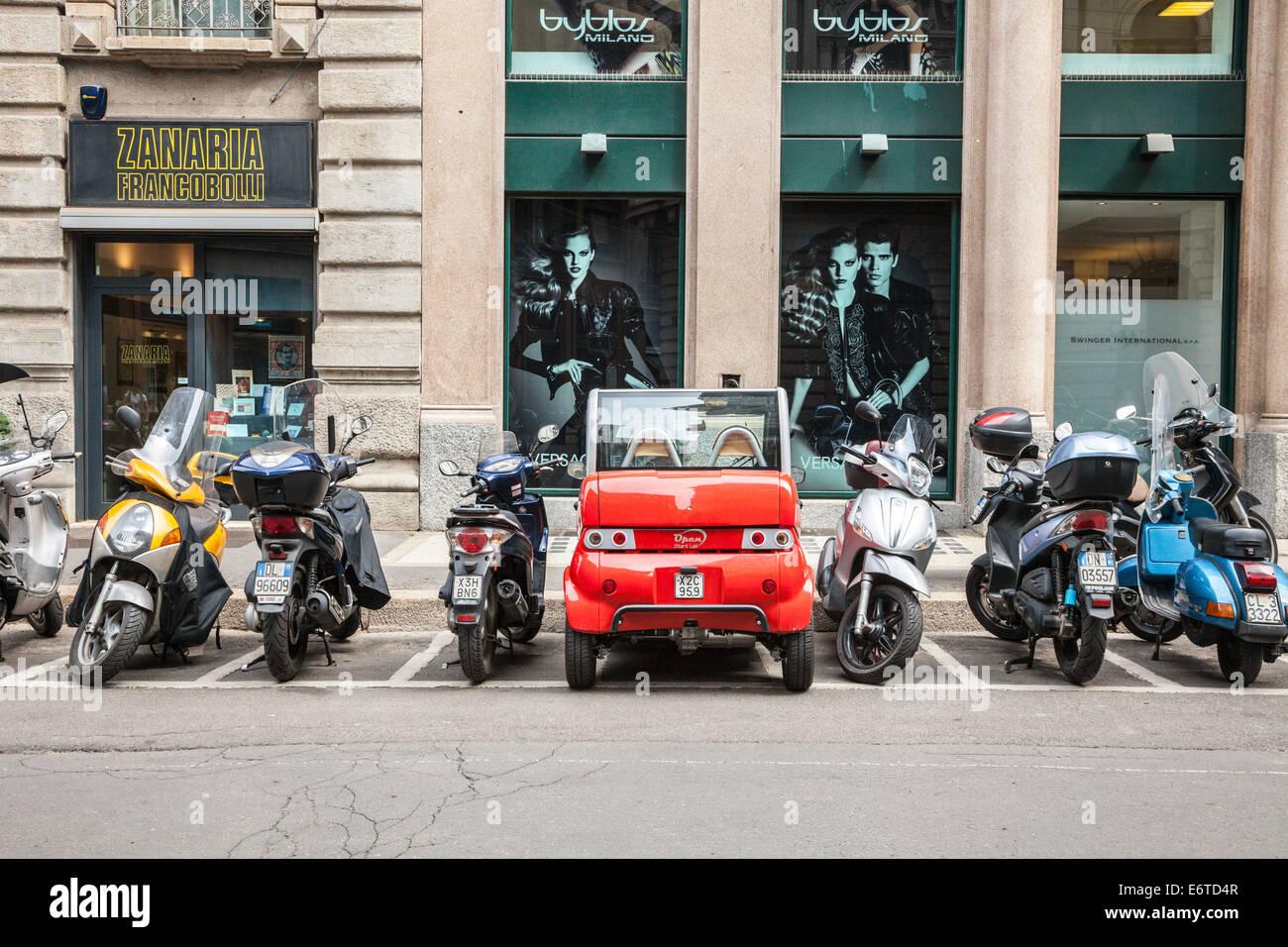 Eléctrico rojo pequeño coche aparcado en una zona de estacionamiento de motocicletas, Milan, Italia. Imagen De Stock