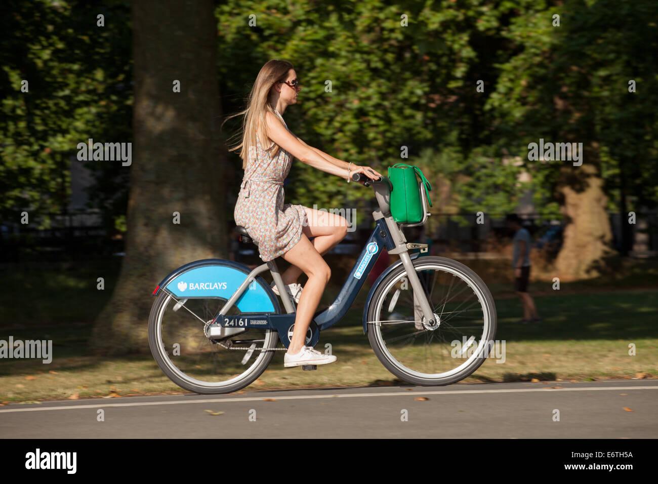 Una mujer ciclista en un alquiler público 'Boris bike' en un parque de Londres Londres - servicio de Imagen De Stock