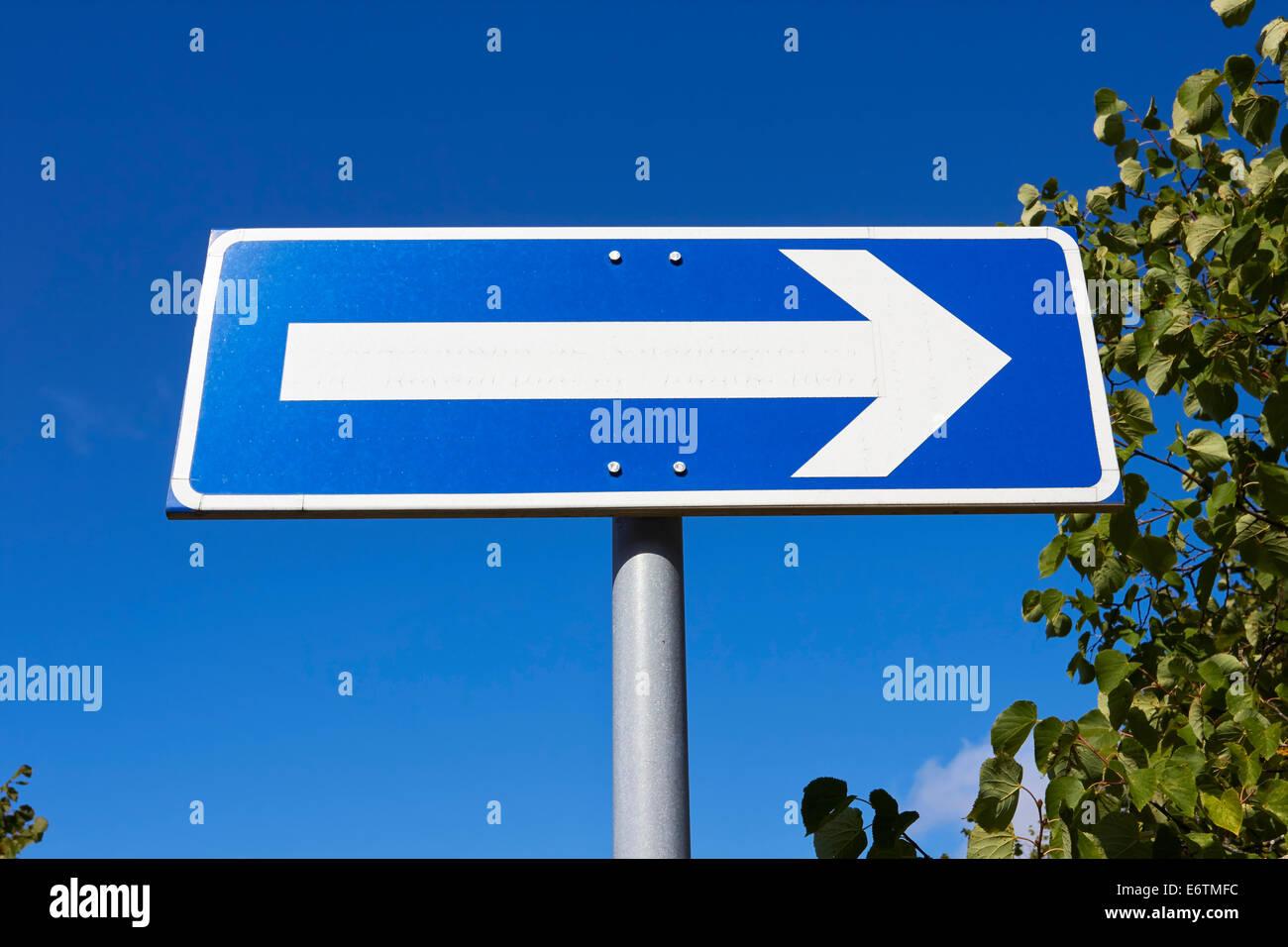 Señal de tráfico flecha orientada hacia la derecha contra el cielo azul Foto de stock