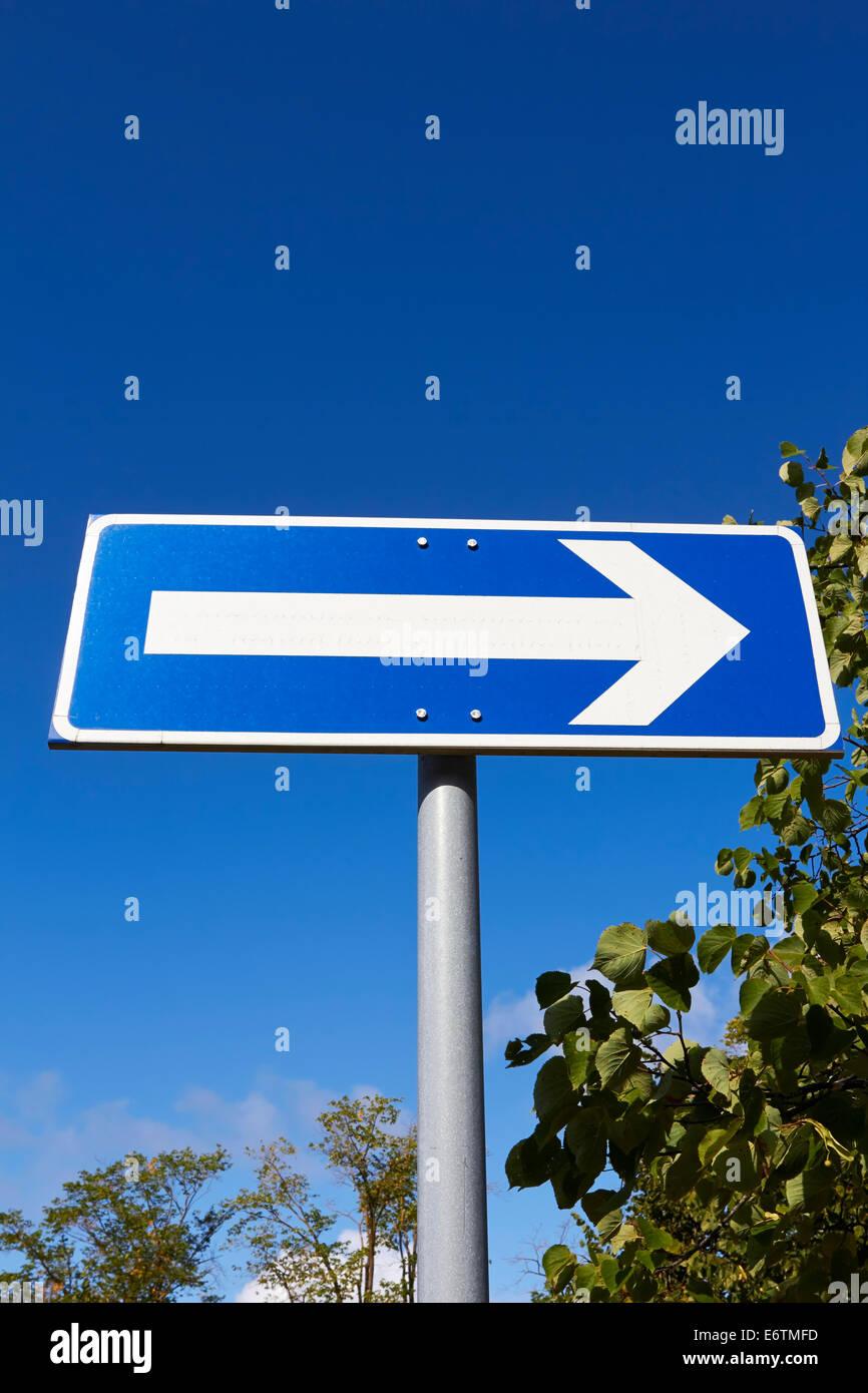 Señal de tráfico flecha orientada hacia la derecha contra el cielo azul Imagen De Stock