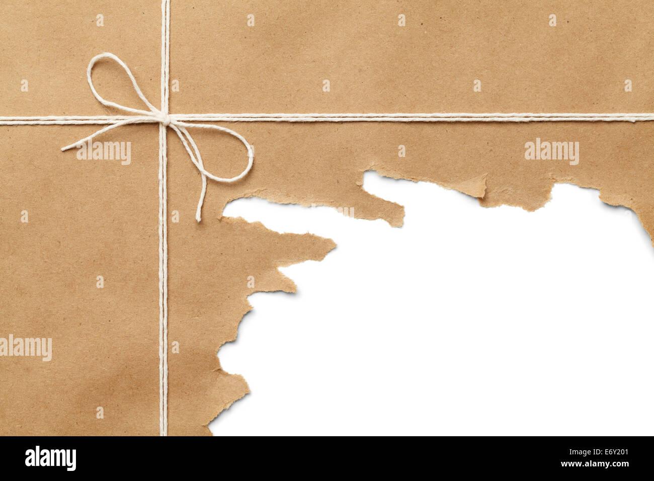 Paquete de papel marrón con una cuerda de desgarre sobre fondo blanco. Foto de stock