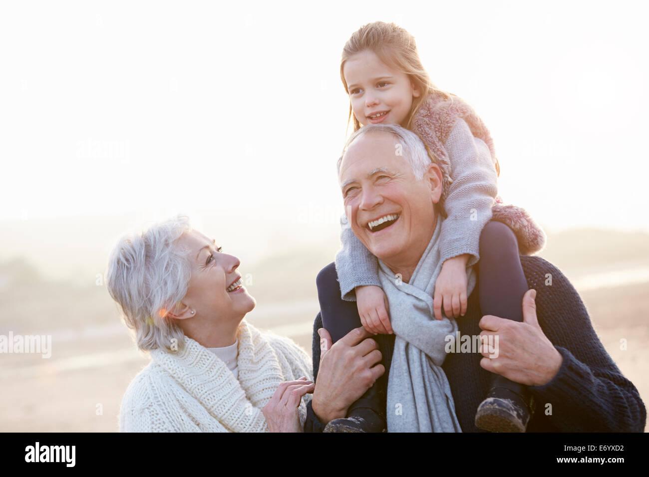 Los abuelos y nieta caminando por la playa de invierno Imagen De Stock