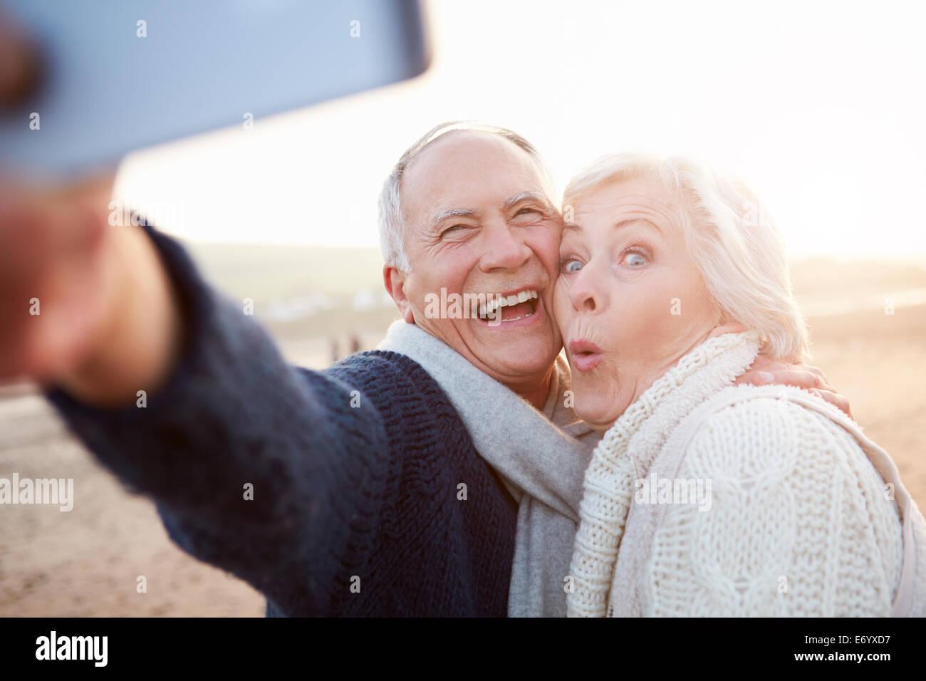 Pareja senior en la playa tomando Selfie permanente Imagen De Stock