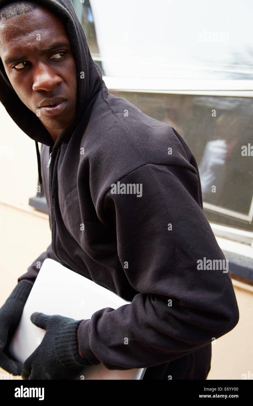 Joven romper y robar el portátil en casa Imagen De Stock