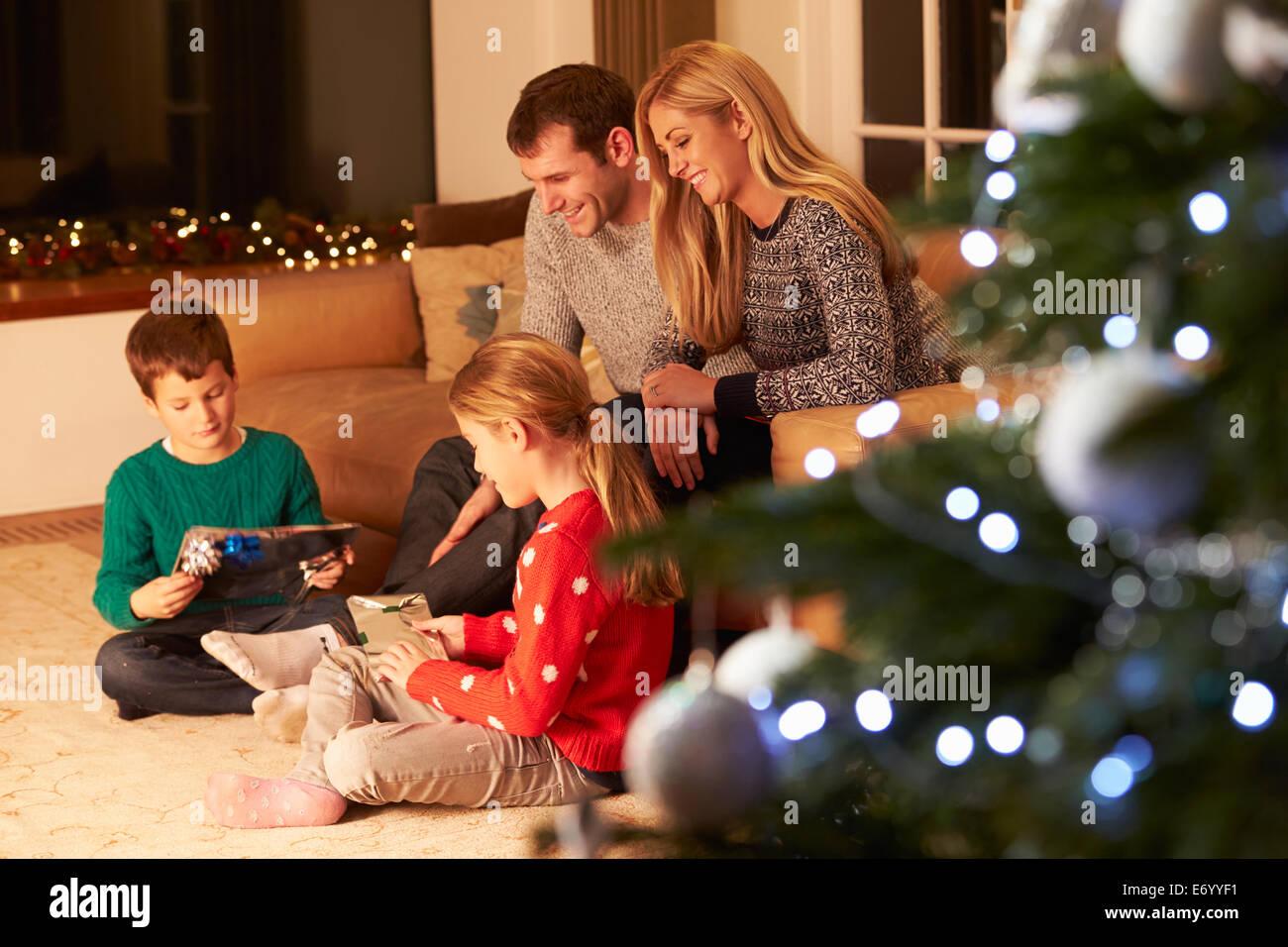Familia desenvolviendo regalos por árbol de Navidad Imagen De Stock