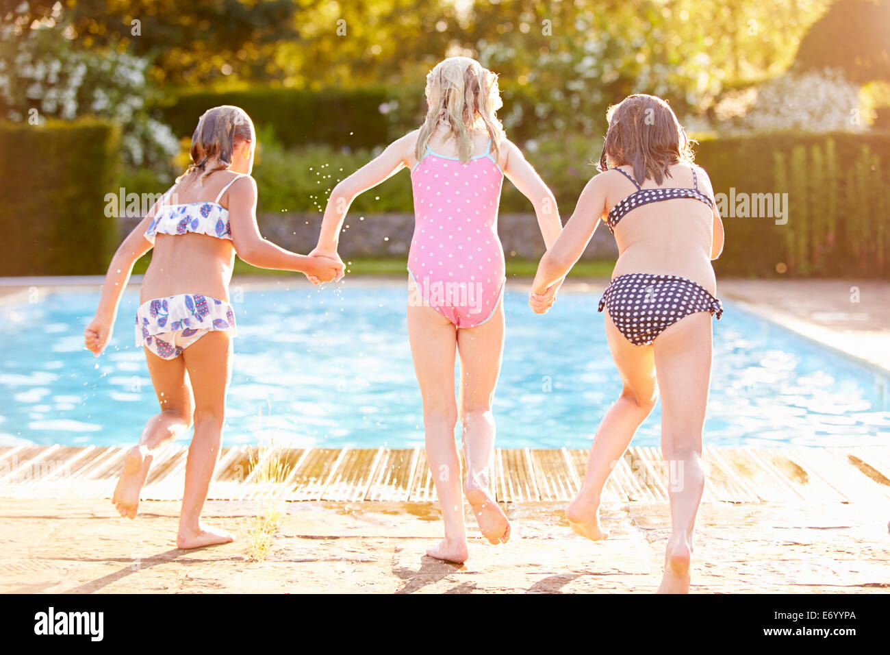 Un grupo de niñas saltando a Piscina Exterior Foto de stock