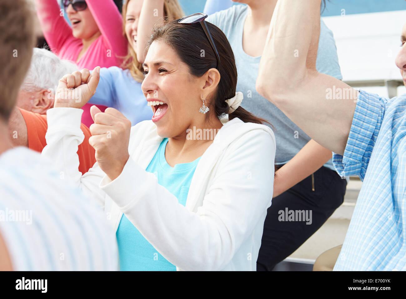 Mujer en la muchedumbre que celebra en evento deportivo Imagen De Stock