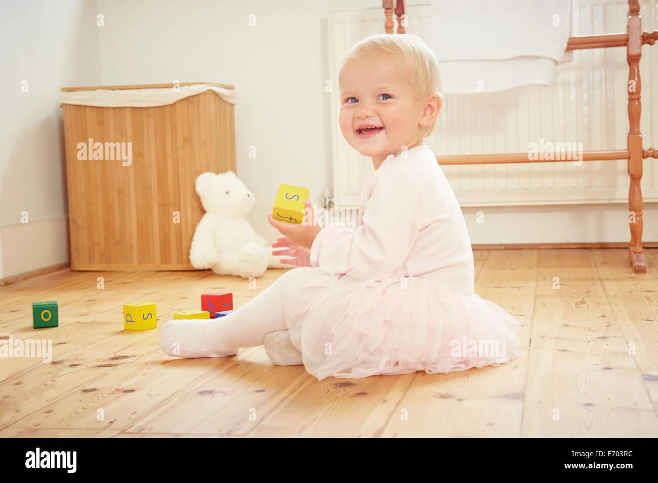 Retrato de la sonrisa de bebé niña jugando en el piso con bloques de construcción Foto de stock