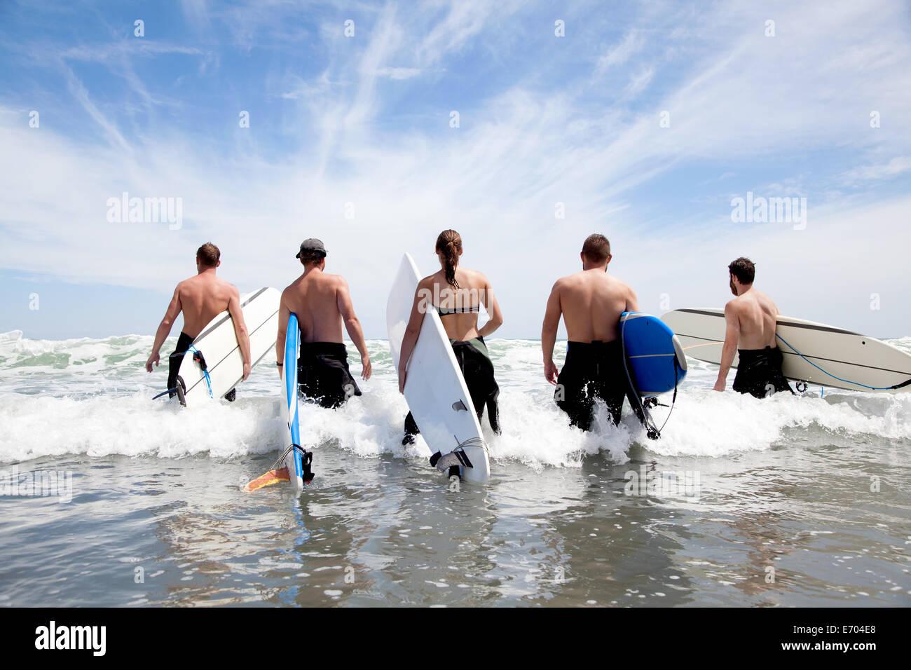 Vista trasera de un grupo de amigos surfistas masculinos y femeninos vadeando en mar con tablas de surf Imagen De Stock