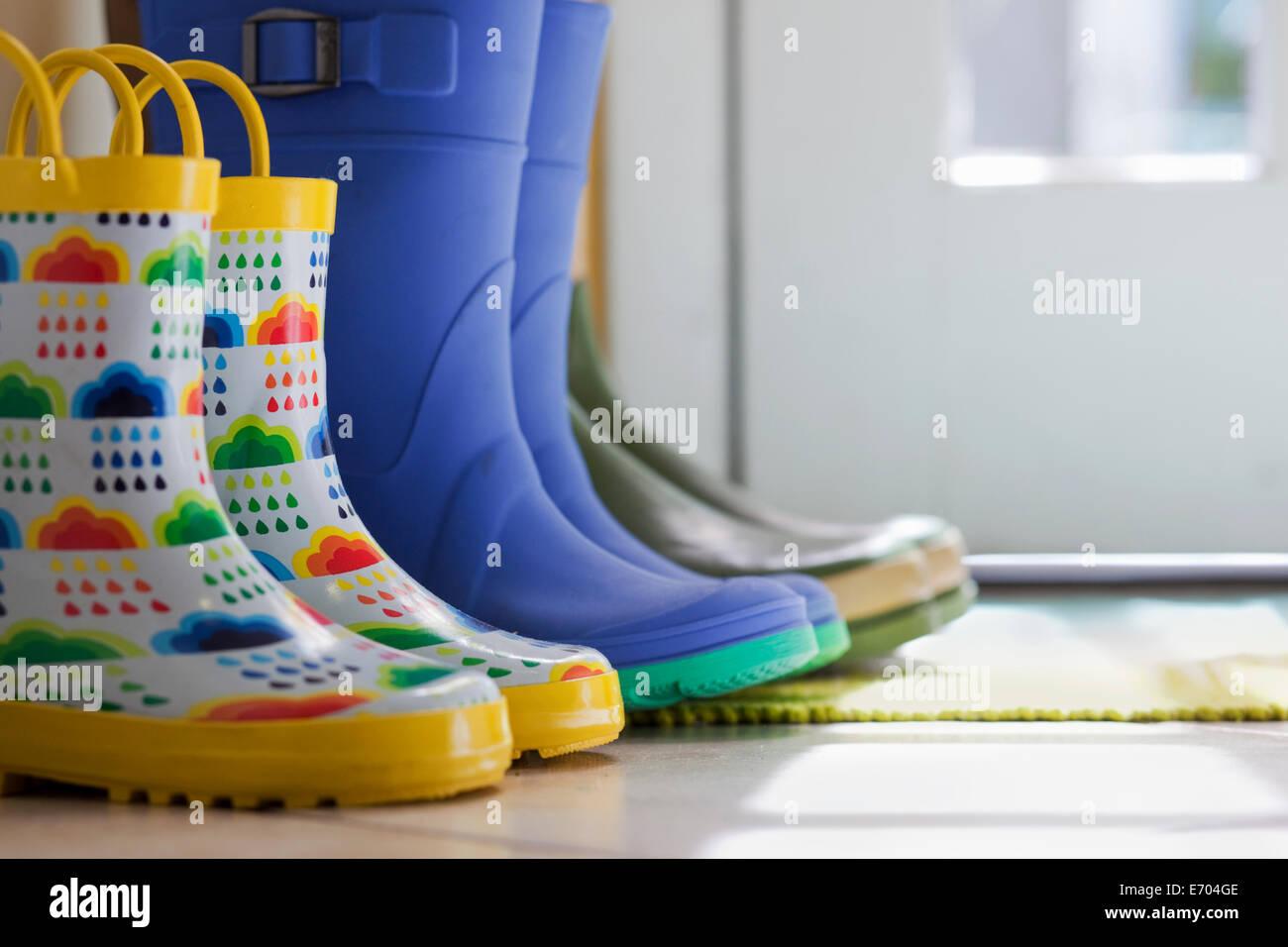 Vista lateral cerca de la hilera de botas de goma en la puerta de atrás Foto de stock