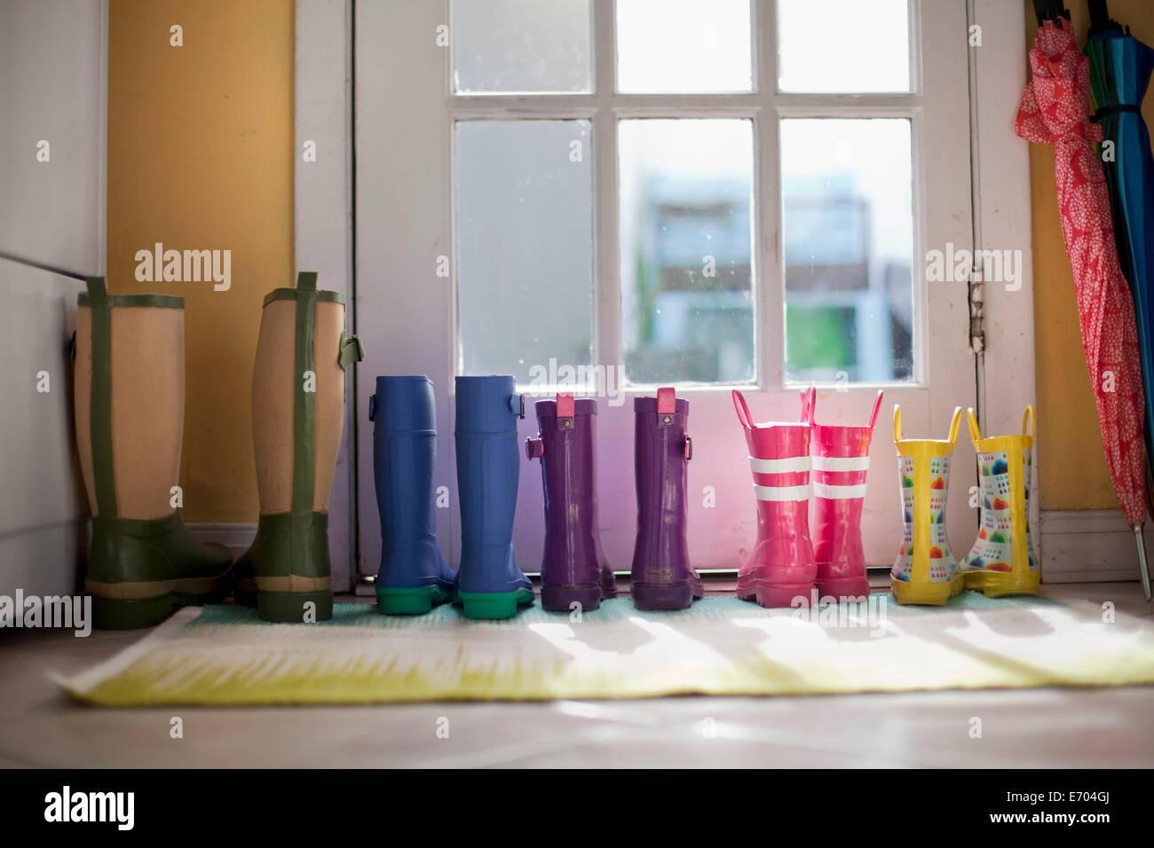 Ordenadas hileras de botas de goma en la puerta de atrás Imagen De Stock