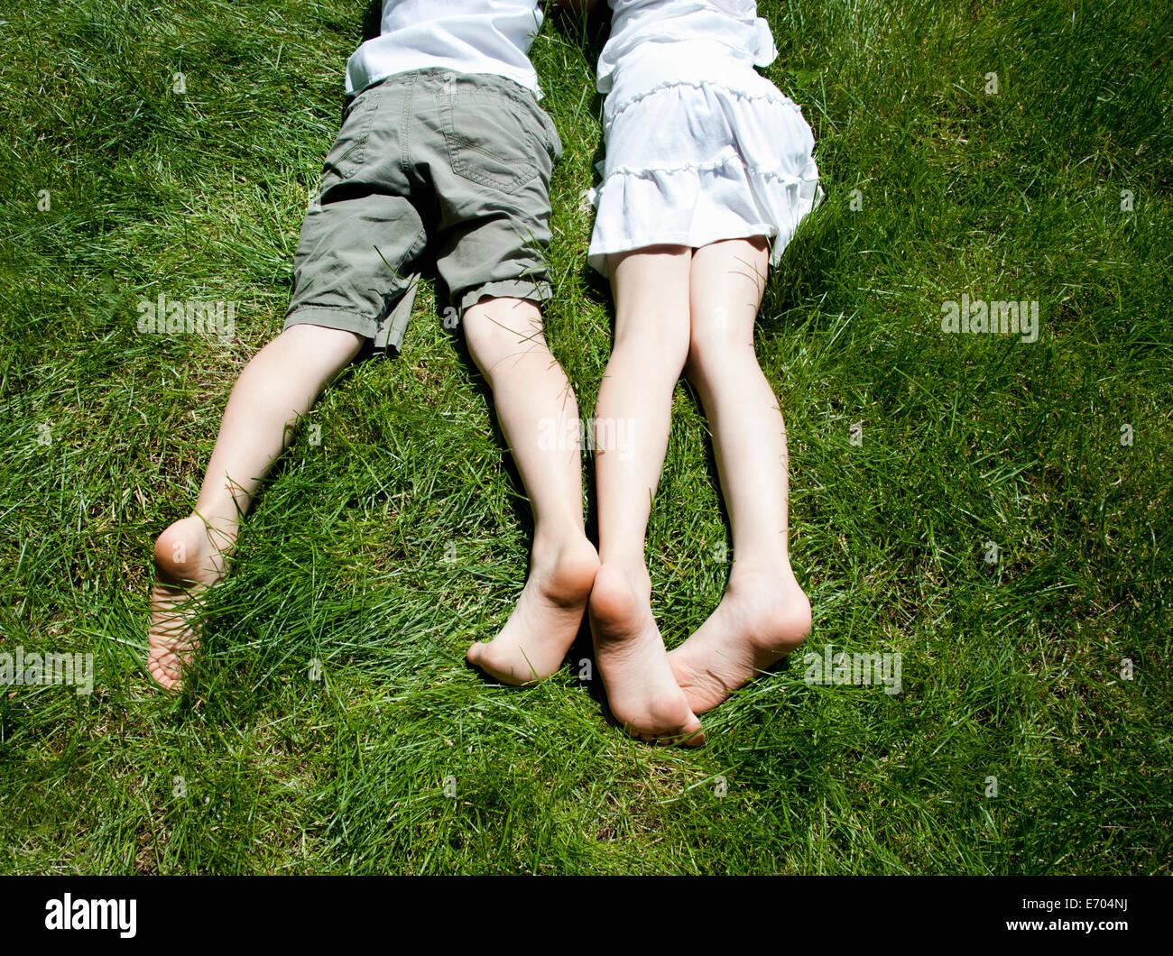 Vista aérea del hermano y hermanas piernas mientras yacían sobre el césped Imagen De Stock