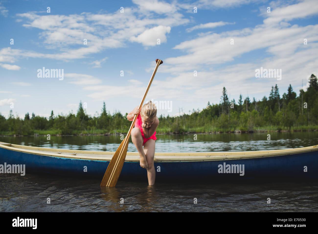 Niña curiosa mirando hacia abajo en el agua en el Indian River, Ontario, Canadá Imagen De Stock