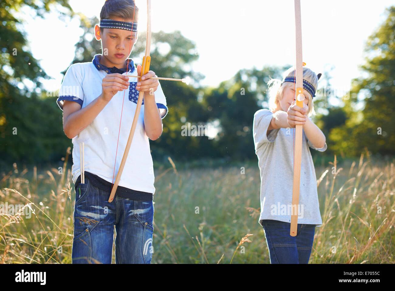 Dos chicos jóvenes la celebración de arco y flecha Imagen De Stock
