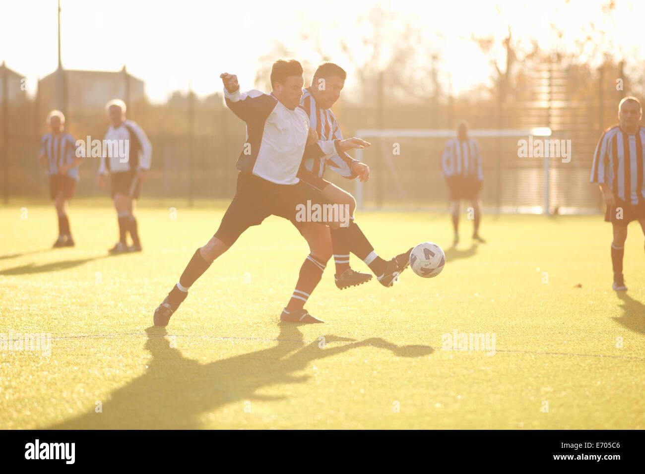 Los jugadores luchan por la pelota de fútbol Foto de stock