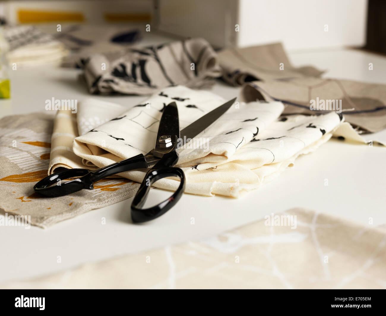 Par de tijeras y tela en la mesa de trabajo Imagen De Stock