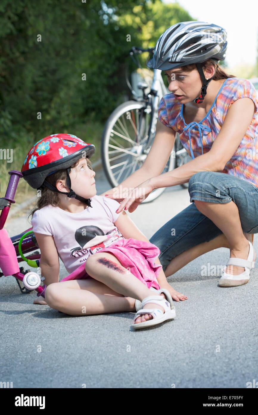 Madre que cuida a su hija caído bicicleta Imagen De Stock