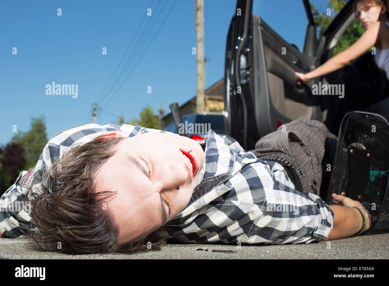 Joven golpeado por coche tumbado en la carretera Foto de stock