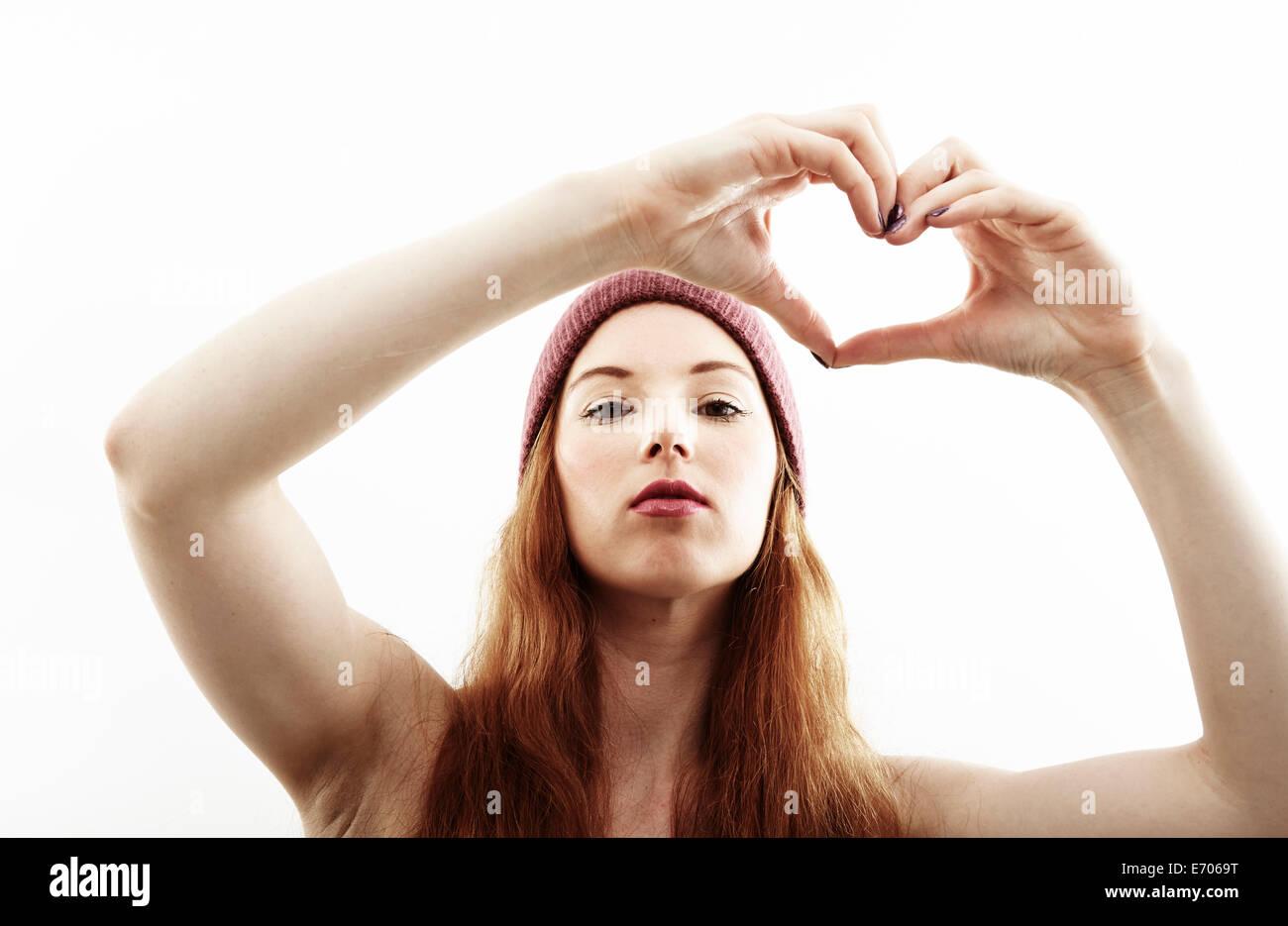 Retrato de estudio de joven mujer haciendo forma de corazón con las manos Imagen De Stock