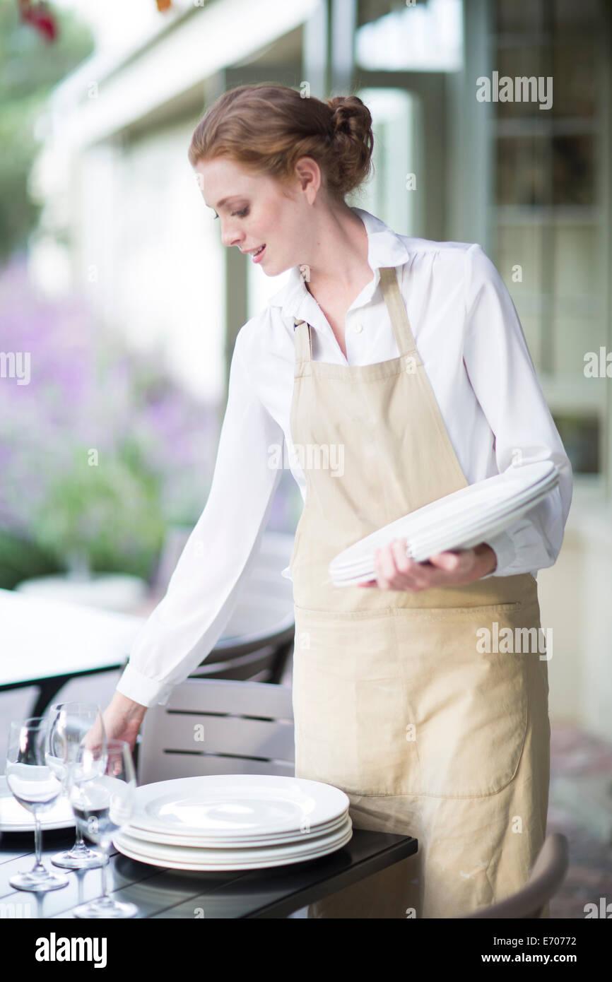 Camarera organizando las placas en la tabla en el restaurante patio Imagen De Stock