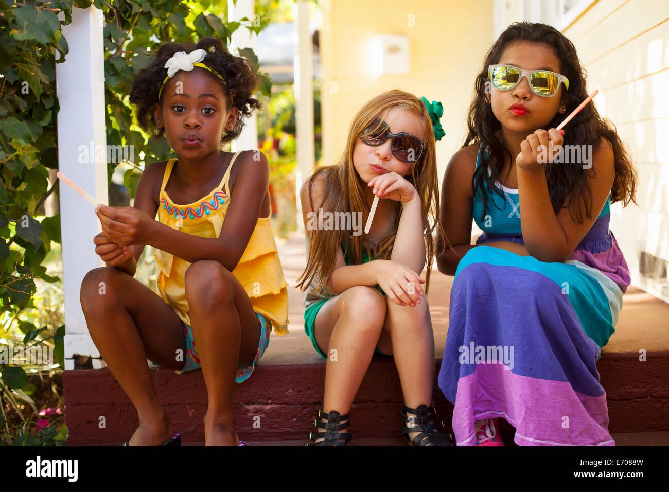 Tres niñas tirando de caras de porche Imagen De Stock
