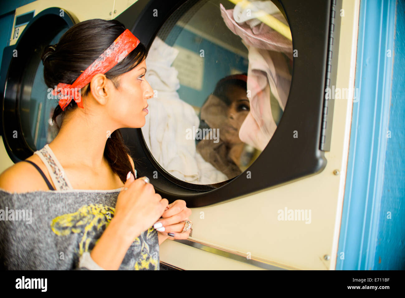 Joven en lavadero, viendo en la máquina de lavado Imagen De Stock