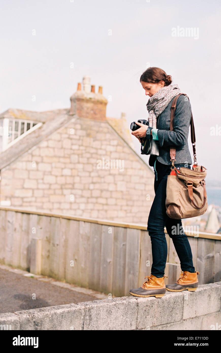 Una mujer con una bolsa grande, sosteniendo una cámara, de pie en la parte superior de una pared. Imagen De Stock