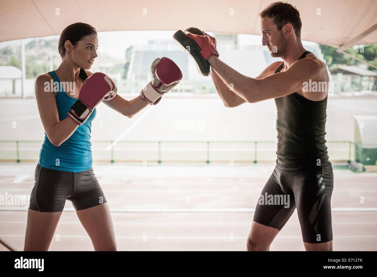 Mujer joven con entrenador personal de boxeo Imagen De Stock