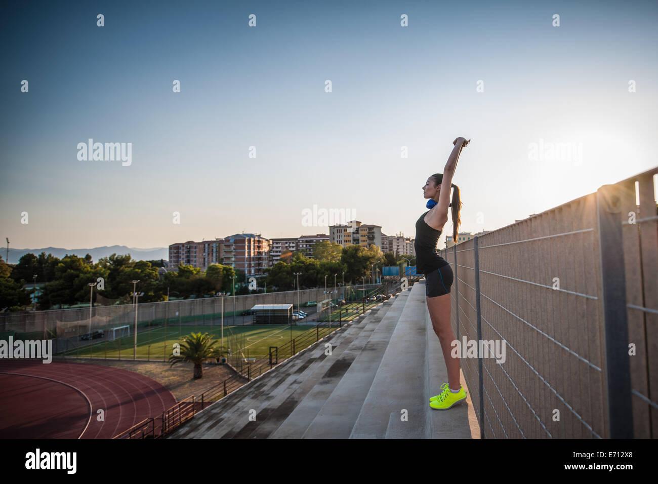 Mujer joven de pie en pasos estirando los brazos hacia arriba Foto de stock