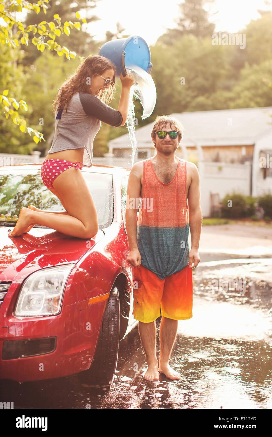Mujer joven verter un cubo de agua sobre la cabeza del hombre. Foto de stock