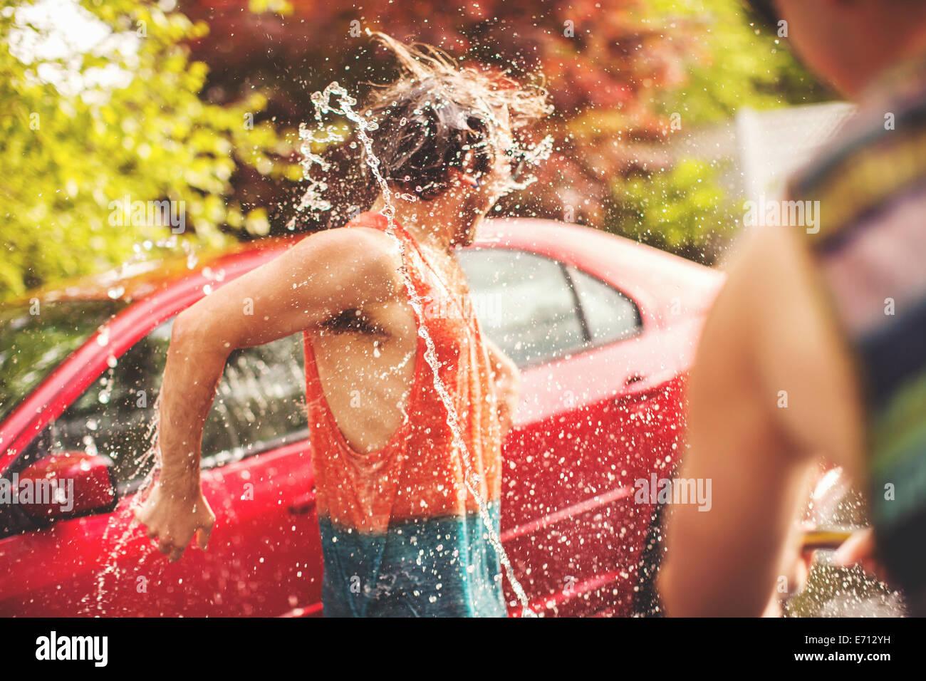 Joven ser rociado con agua Imagen De Stock