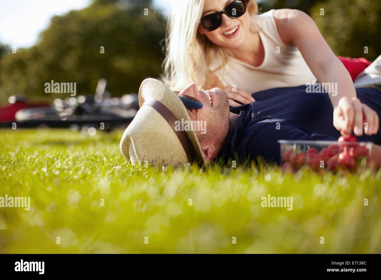 Mujer joven alcanzando las fresas mientras novio tumbado en el parque Imagen De Stock