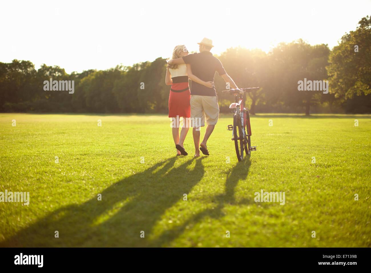 Par pasear mientras empuja la bicicleta en el parque Foto de stock
