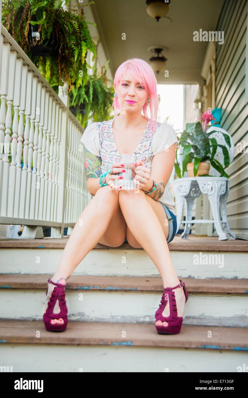 Retrato de mujer joven con el pelo rosa sentado en el porche pasos Imagen De Stock