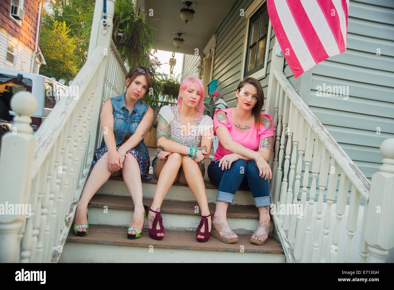 Retrato de amigas jóvenes sentados en el porche pasos Imagen De Stock