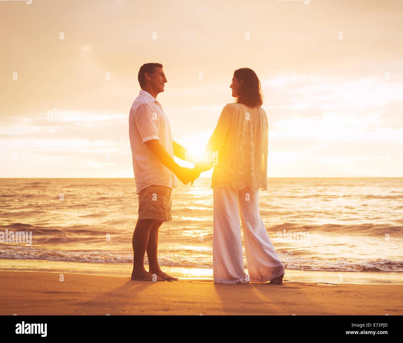 Romántica pareja disfrutando del atardecer en la playa. Imagen De Stock