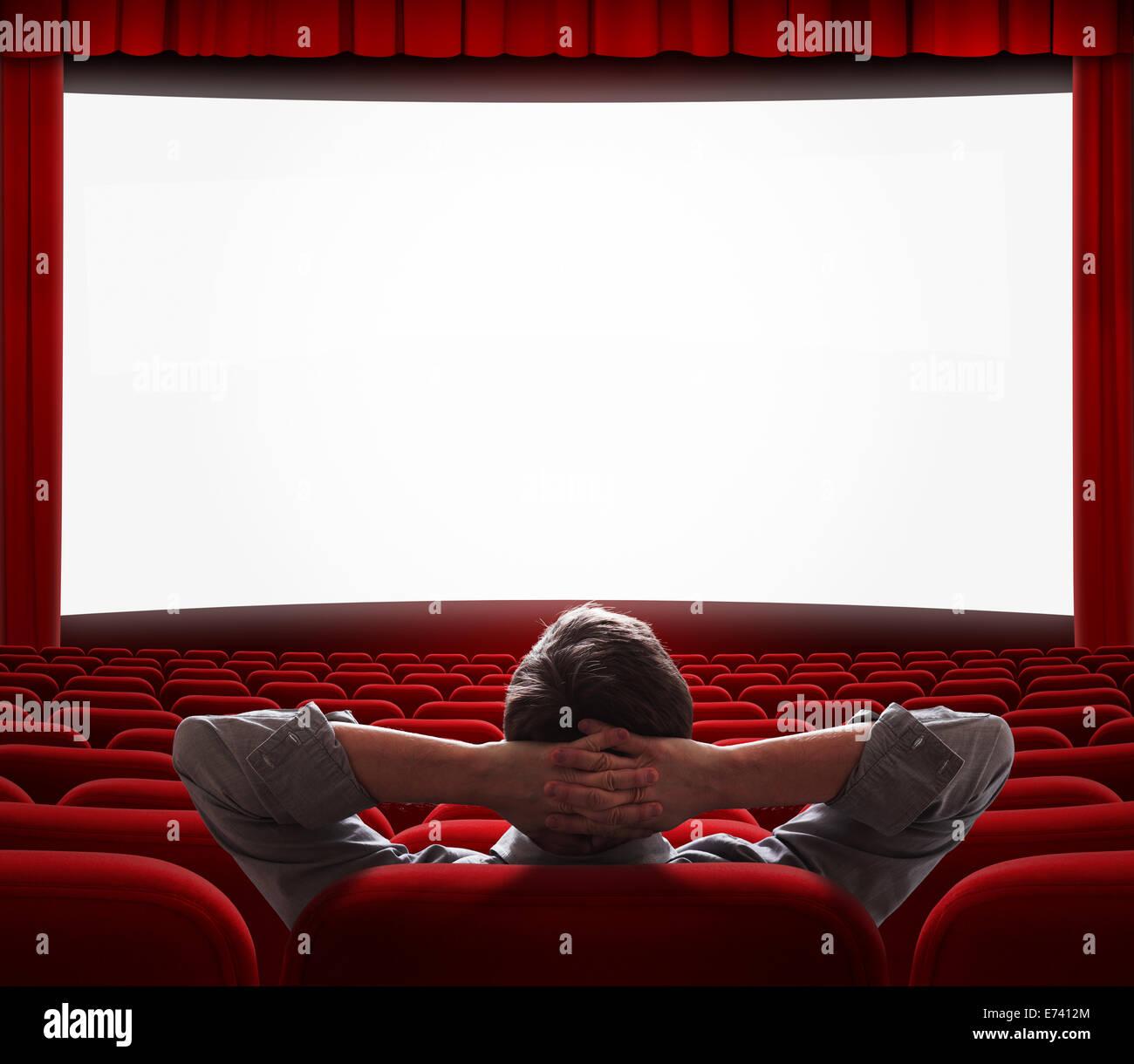 Uno relajado hombre sentado solo con confort como en casa delante de la pantalla grande en la sala de cine vacía Imagen De Stock