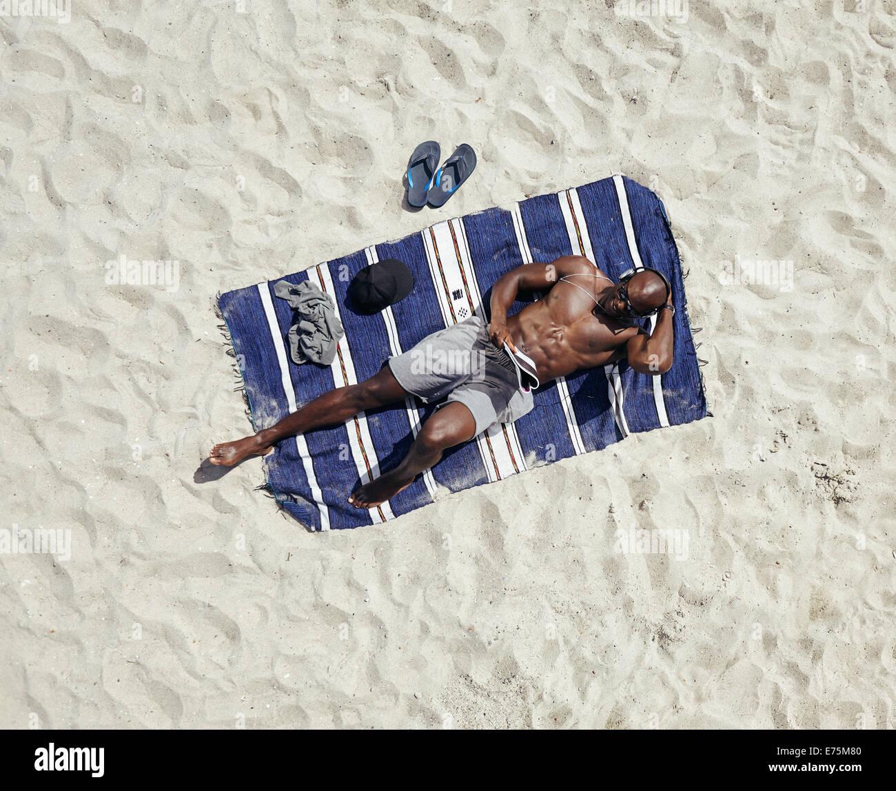 Vista superior del chico descamisado acostado sobre una estera leyendo una revista. Modelo masculino africano relajándose Imagen De Stock