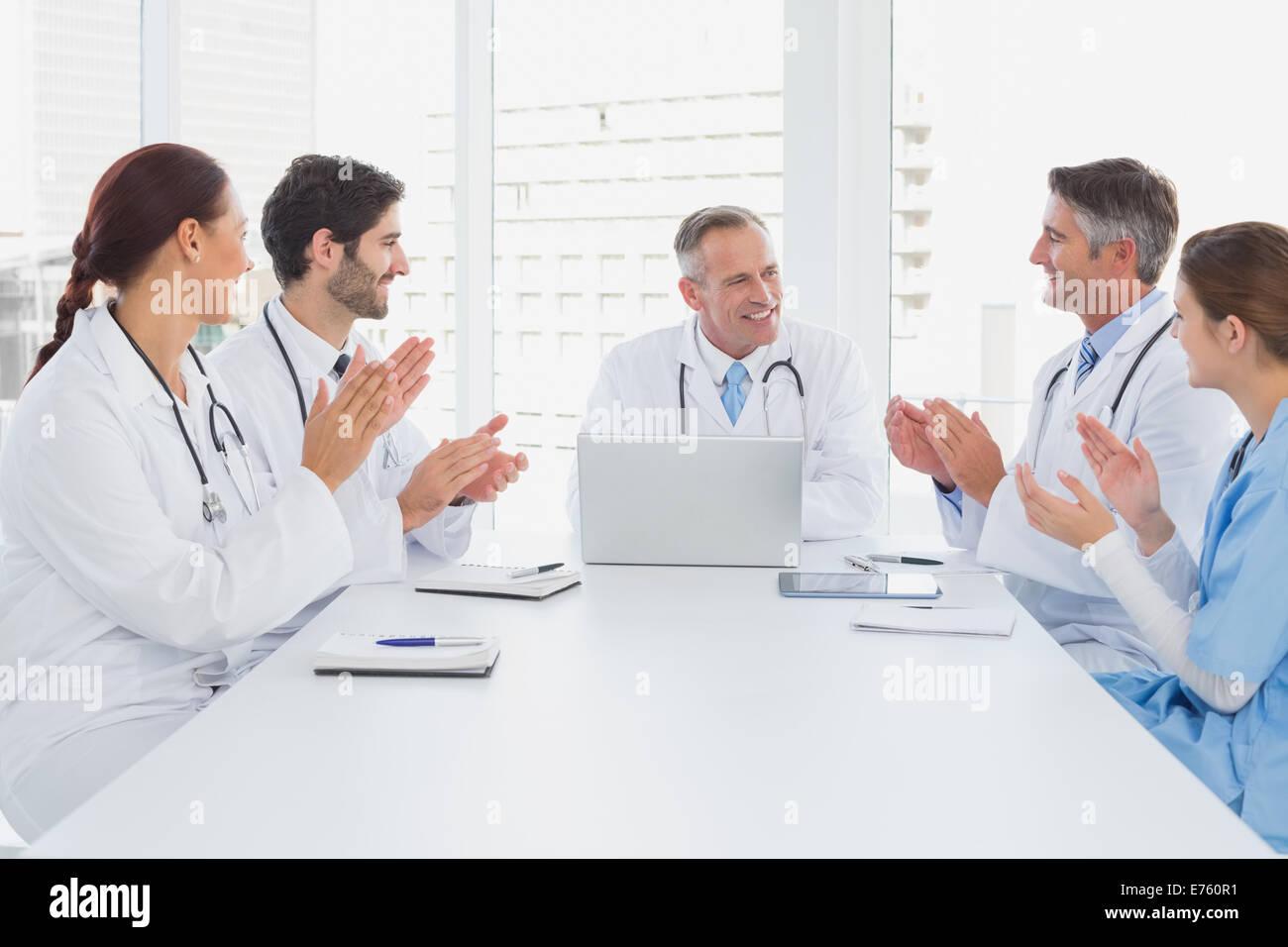 Los doctores aplaudiendo a un colega médico Imagen De Stock