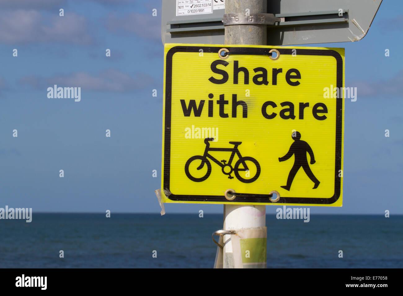 """'Share con cuidado"""" signo en paseo marítimo compartido por ciclistas y caminantes. Seaford, Sussex. Imagen De Stock"""