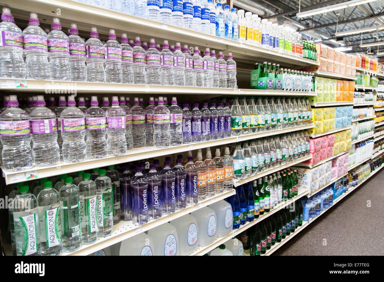 Una tienda de alimentos naturales pasillo con estantes de agua embotellada. Imagen De Stock