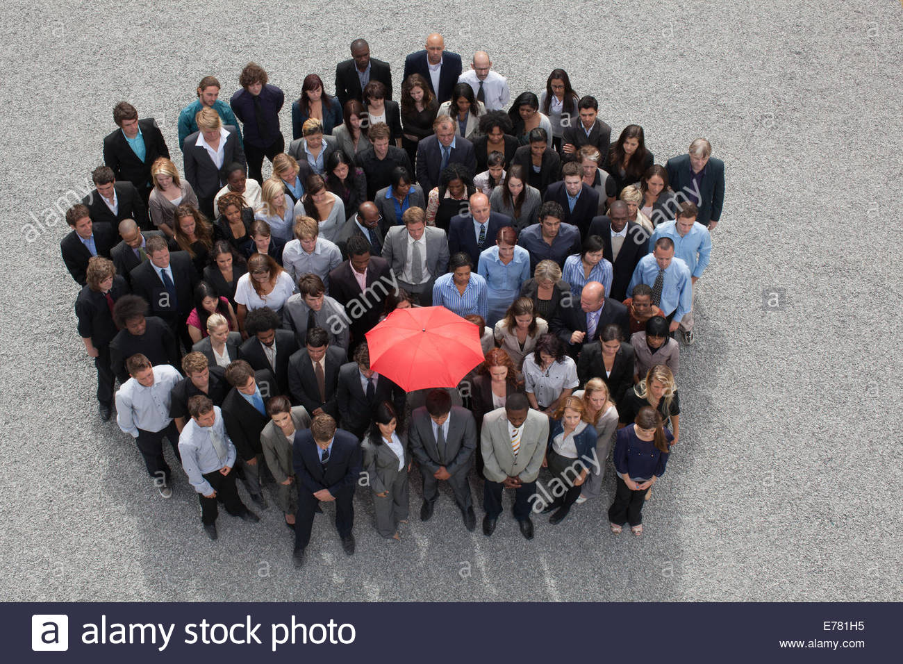 Paraguas en el centro del círculo formado por gente de negocios Imagen De Stock