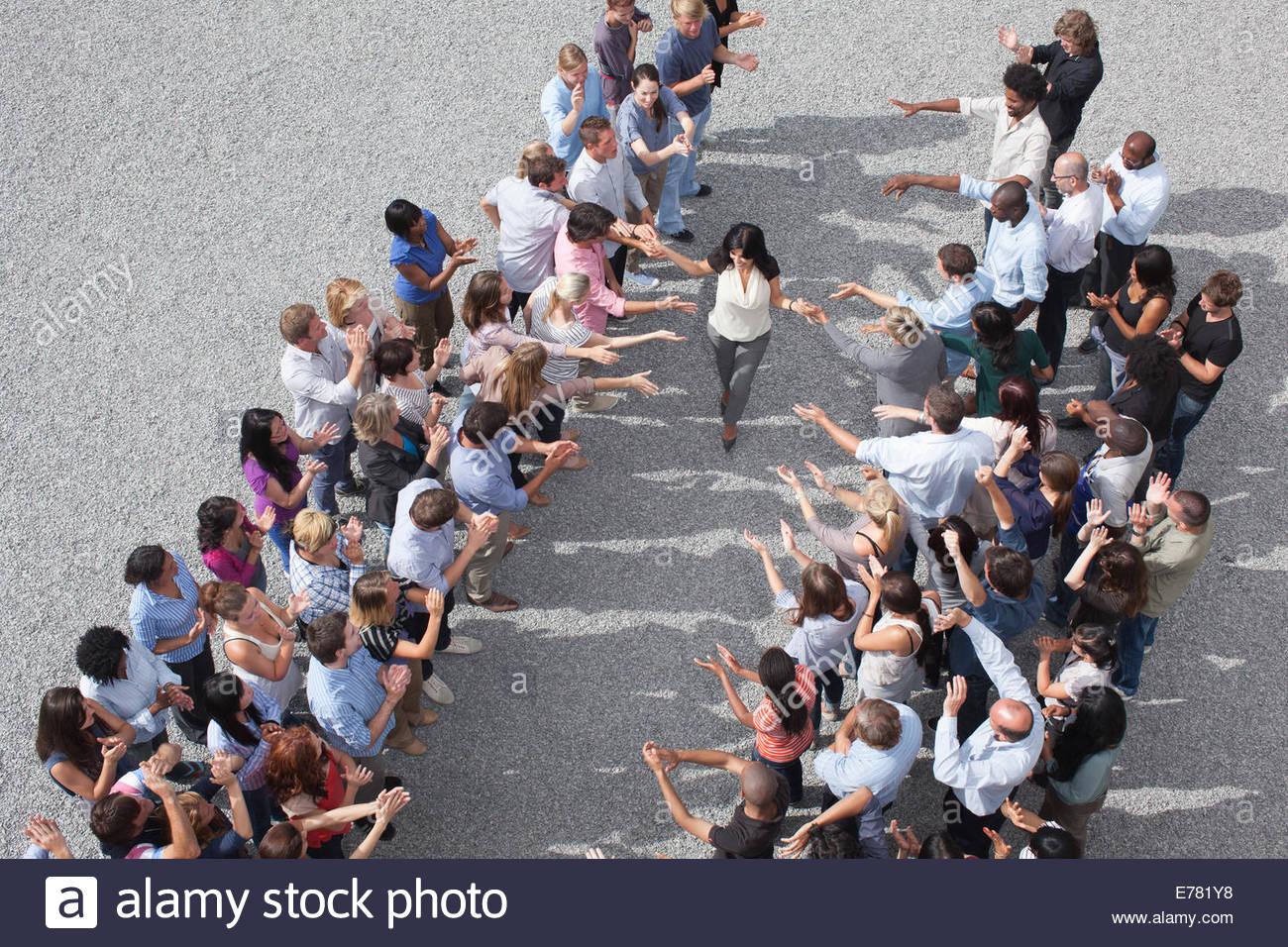 Mujer caminando entre dos grupos de personas, las palmas Imagen De Stock